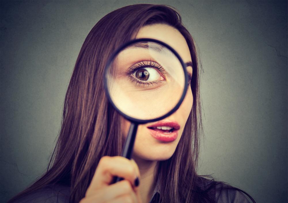 虫眼鏡を手にする女性